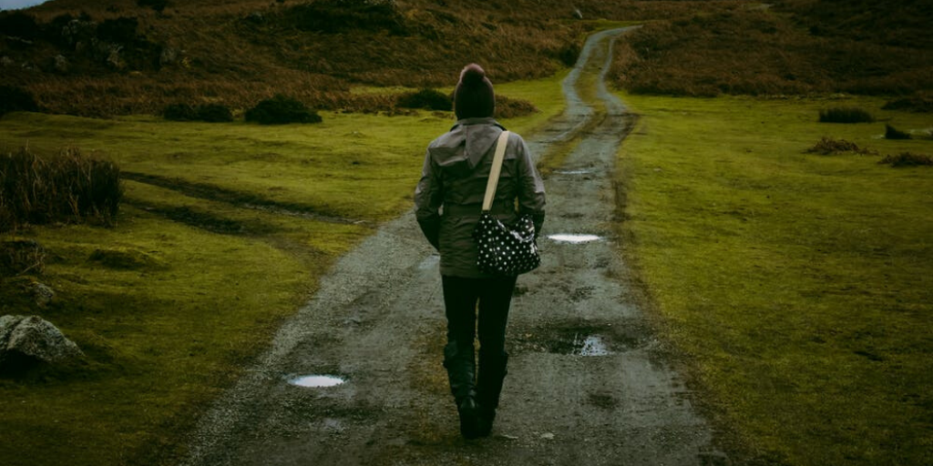 A woman walks alone down a long gravel path in the countryside